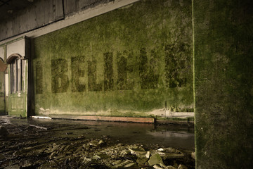 text i believe on the dirty wall in an abandoned ruined house