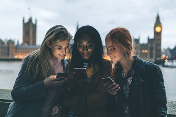 Best friends girls with smartphones in London