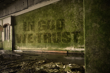 text in god we trust on the dirty wall in an abandoned ruined house