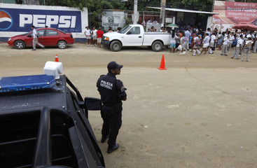 Policeman stands guard outside a school at an impoverished neighbourhood in Acapulco