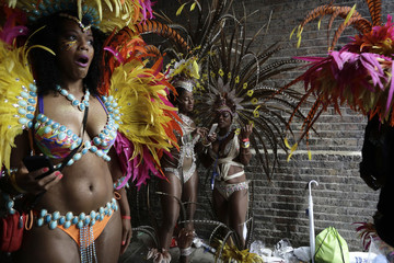 A performer reacts to a rain storm at the Notting Hill Carnival