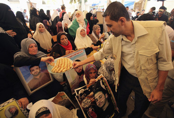 A man hands out sweets to Palestinian women holding pictures of their jailed sons during a demonstration calling for their release at the International Red Cross headquarters in Gaza City