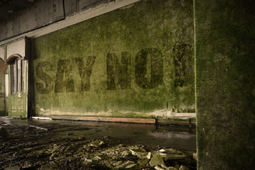 text say no on the dirty wall in an abandoned ruined house