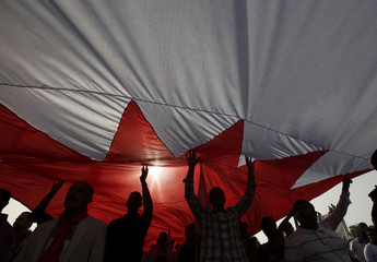 Anti-government protesters hold a Bahraini flag over their heads during an anti-government rally in Budaiya