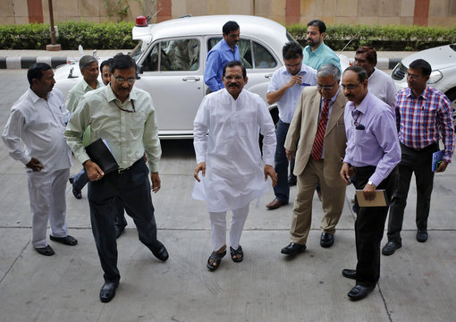 Shripad Naik, India's new minister in charge of the department of AYUSH, is flanked by his officials as he arrives to take charge of his office in New Delhi