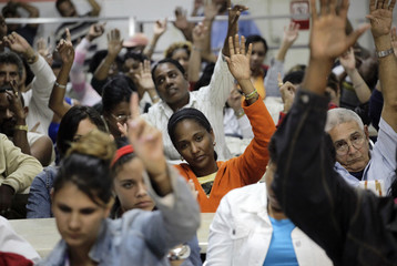 Employees vote during a debate on new guidelines for the Cuban economy in Havana