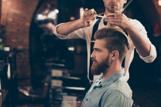 Profile view of a red bearded stylish barber shop client. He is getting his perfect trendy haircut from a classy stylist, looking in a mirror and waiting for result