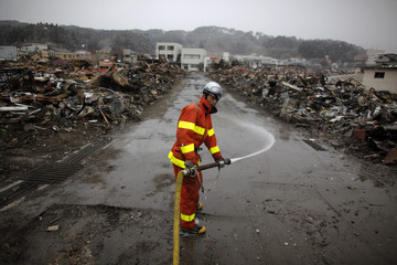 A fireflighter sprays water to clean a street in the debris in Yamada
