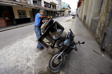 A man repairs a motorcycle with a sidecar on a street in Havana