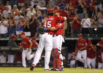 Texas Rangers' Holland hugs Pierzynski after pitching a complete game shut out during their MLB American League baseball game in Arlington