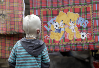 """Wang Gengxiang, known as """"Masked Boy"""", looks at a cartoon picture of little bears on a quilt cover on the outskirts of Fenyang"""