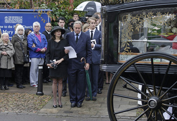 The son and the widow of the 11th Duke of Marlborough, John Spencer-Churchill, watch as his coffin is loaded onto a horse drawn carriage outside the Parish Church of St. Mary Magdalene following his funeral service, in Woodstock