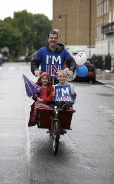 A Remain supporter cycles, with two children, along the the road in which former London mayor, Boris Johnson, lives, on the day of the EU referendum, in London