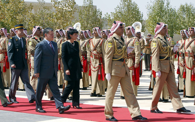 Jordan's King Abdullah and Switzerland's President and Economy Minister Leuthard review Bedouin honour guards upon her arrival at the Royal Palace in Amman