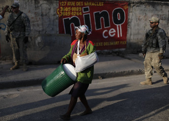 A woman holds a bucket after a supplies distribution from an international humanitarian organization called Catholic Relief Services (CRS) in Port-au-Prince