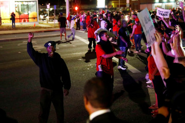 A man wearing a hat of the New Black Panther Party raises his fist while protesters block an intersection as people march to protest the death of Alfred Olango, who was shot by El Cajon police on Tuesday