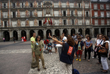 A guide conducts a tour for visitors at Madrid's Plaza Mayor