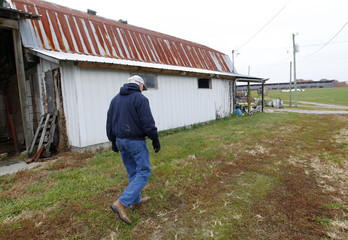 A retired dairy farmer walks past an old dairy barn on the farm where he still raises soybean and hay, in Hillsboro, Kentucky