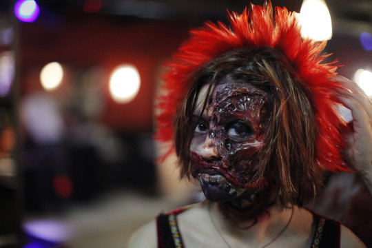 A woman dressed up as a zombie poses for a picture during an event in New York