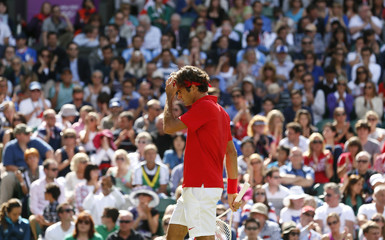 Switzerland's Federer pauses during the men's singles tennis gold medal match against Britain's Murray at the All England Lawn Tennis Club during the London 2012 Olympic Games