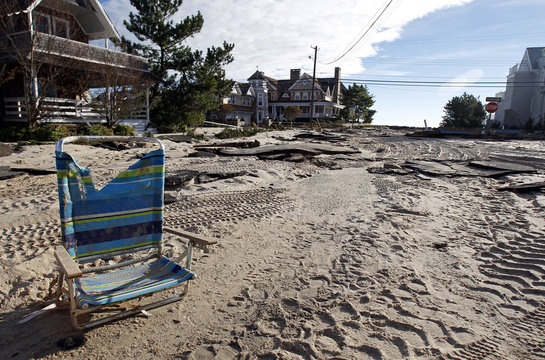 A lone beach chair is seen in the middle of a sand covered road, as part of the damage caused by Hurricane Sandy is seen in Bay Head
