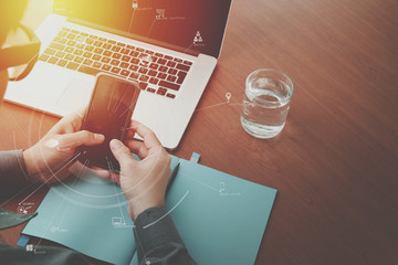 top view of  businessman hand working with laptop computer and mobile phone with VR business strategy concept on wooden desk