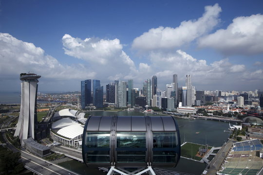 Tourists sit in a capsule on the Singapore flyer observatory wheel overlooking the skyline of the central business district in Singapore