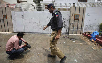 A policeman gestures to a cameraman filming at the site of a bomb explosion in Karachi