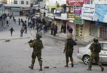 Israeli soldiers walk with their weapons behind a group of Palestinians during clashes in Hebron