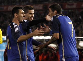 Argentina's Messi, Gago and Di Maria celebrate their team's first goal against Trinidad and Tobago during their friendly match in Buenos Aires