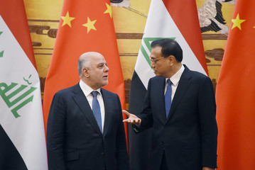 Iraqi Prime Minister Haider al-Abadi talks with Chinese Premier Li Keqiang as they attend a signing ceremony at the Great Hall of the People in Beijing