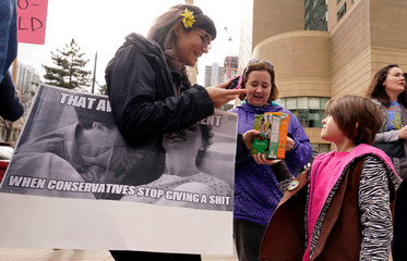 Girl Scout Lucy Bassett sells boxes of Girl Scout cookies to a Planned Parenthood supporter at a protest in downtown Denver