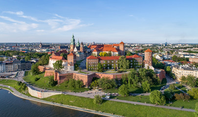 Krakow, Poland. Wawel hill with historic royal castle and cathedral, Vistula River, park and walking people. Aerial view at sunset.