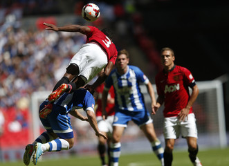 Manchester United's Patrice Evra flies over Wigan Athletic's Shaun Maloney during their English Community Shield soccer match at Wembley Stadium in London