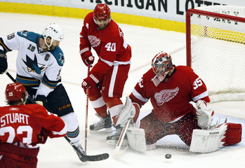 Red Wings' Howard makes a save on Sharks' Thornton as center Zetterberg looks to clear the rebound during Game 6 of the NHL Western Conference semi-final hockey playoff in Detroit