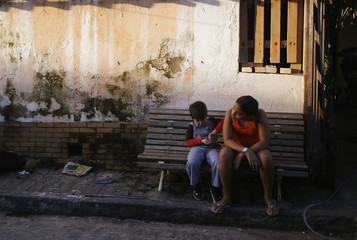 A girl and a boy sit on a bench in Olinda