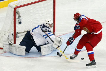 Finland's goaltender Kosikinen saves in front of Russia's Tikhonov during the first period of their men's ice hockey World Championship group B game at Minsk Arena in Minsk