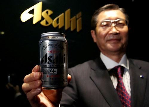 Asahi Group Holdings President and COO Koji poses for a photo with an Asahi Super Dry beer can at its headquarters in Tokyo