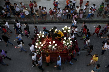 Devotees walk with a statue of Black Nazarene on a carriage during a procession as part of Holy Week celebrations in Boac, Marinduque in central Philippines