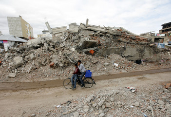 People cycle past a collapsed building in Ercis near the eastern Turkish city of Van