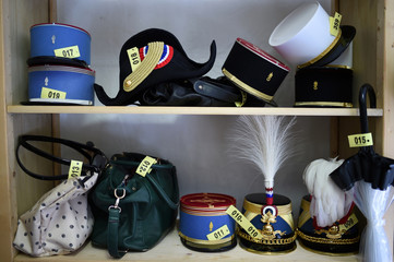 A picture shows a bicorn hat, an umbrella, bags and different types of flat-topped French military caps in a cloakroom at the Defence ministry in Paris during the annual reception in honour of the French Armed Forces