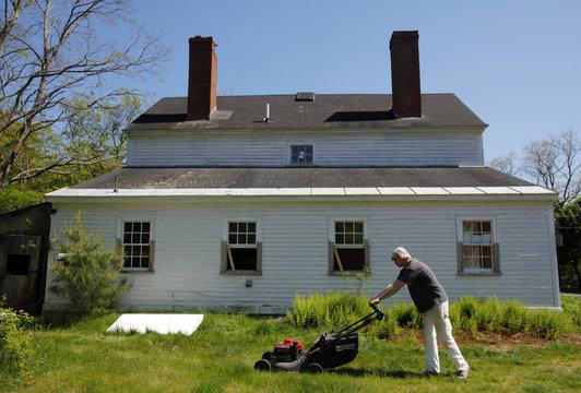 Kaminski mows the lawn outside his home, a pre-Victorian farmhouse called  Dodge House, in Hamilton