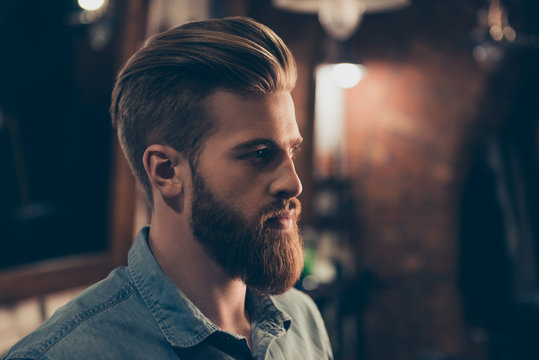 Barbershop concept. Profile side portrait of attractive severe brutal red bearded young guy. He has a perfect hairstyle, modern stylish haircut
