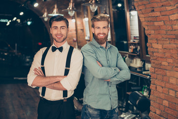 Welcome to barber shop! Red bearded handsome young man in a casual jeans outfit and attractive brunette dressed classy are standing with the crossed hands