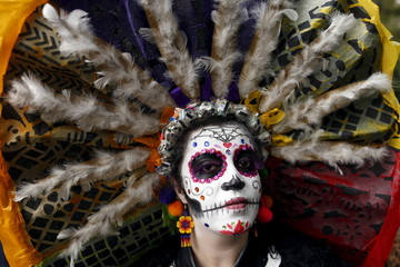"A woman with her face painted to look like the popular Mexican figure called ""Catrina"", poses for a photograph as she takes part in the annual Catrina Fest in Mexico City"