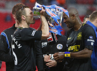 Wigan Athletic's Callum McManaman drinks from the trophy after his club defeated Manchester City in their FA Cup final soccer match at Wembley Stadium in London
