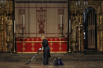 A woman vacuums at the high altar of Westminster Abbey in central London