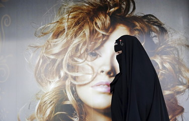 Gisele Marie, a Muslim woman and professional heavy metal musician, walks past a poster after a rehearsal at her house, in Sao Paulo