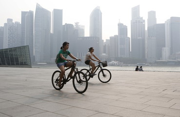People ride bicycles past the central business district shrouded in haze in Singapore