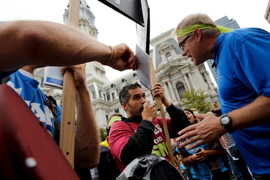 """A man chants """"Jesus loves you"""" over and over to a pair of anti-Catholic demonstrators, outside the secured area surrounding Pope Francis as he celebrates mass in Philadelphia"""